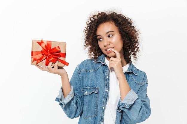 Портрет довольно задумчивой случайной африканской девушки, стоящей изолированно над белой стеной и держащей подарочную коробку