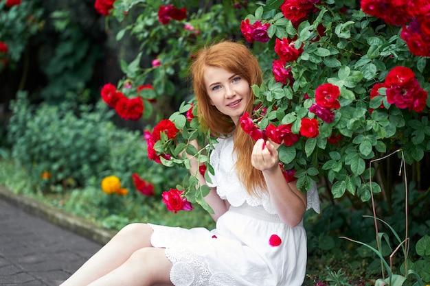 咲くバラの背景に白い光のドレスを着たかわいい赤毛の女の子の肖像画。