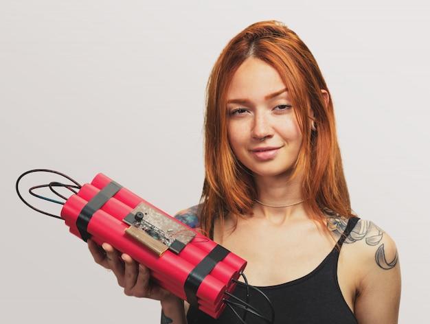 Портрет красивая рыжая девушка держит динамит