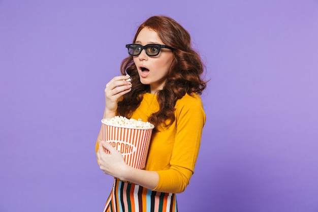 Портрет довольно шокированной молодой рыжеволосой женщины, стоящей над фиолетовым