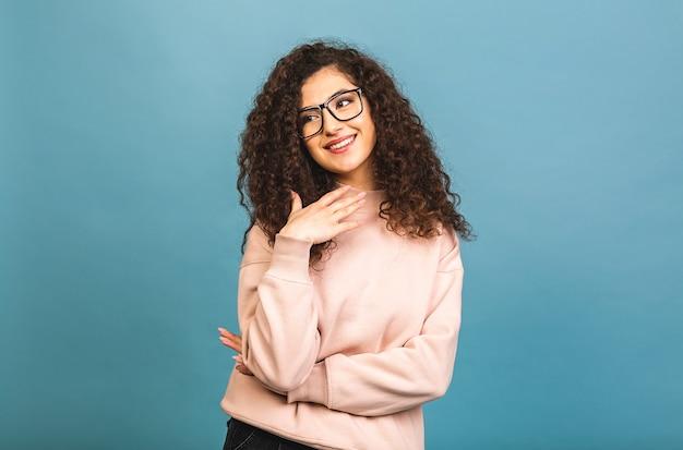 青い背景に分離されたカジュアルなポーズでかわいい笑顔の巻き毛の若い女性の肖像画。