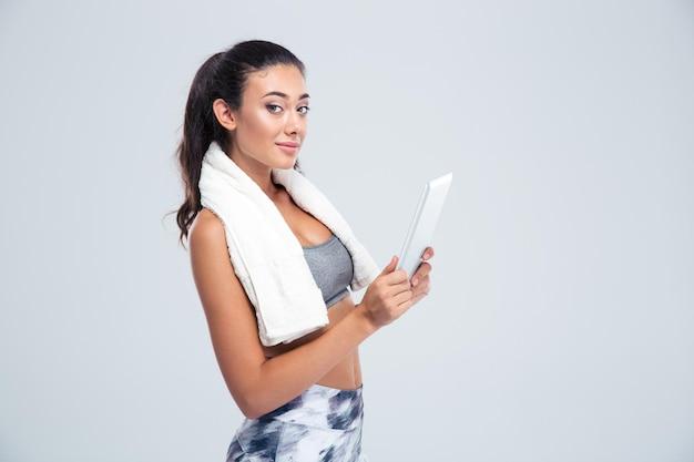 白い壁に分離されたタブレットコンピューターを使用してかわいいスポーツ女性の肖像画