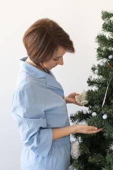 Портрет красивой женщины, украшающей елку