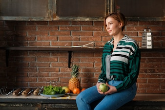 Portrait of a pretty woman holding apple while sitting on kitchen table.