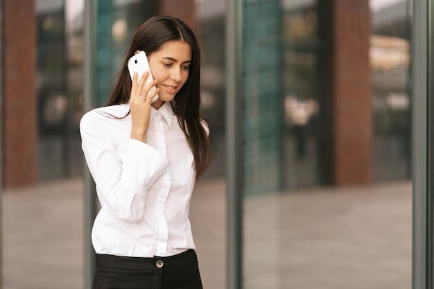 Портрет красивой женщины, говорящей по телефону в белой деловой рубашке. обсуждение повседневных задач с коллегами со стеклянными стенами.