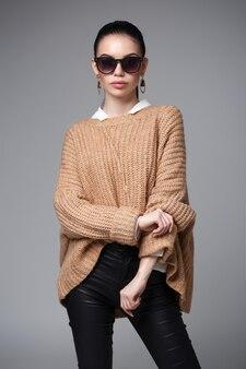Портрет красивой женщины. стильная молодая женщина в свитере и солнцезащитных очках