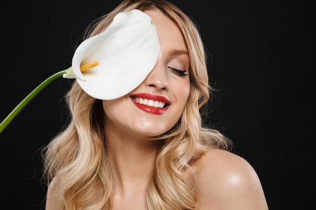 白い花を保持している孤立したポーズをとって明るい化粧赤い唇を持つかなり若いブロンドの女性の肖像画。