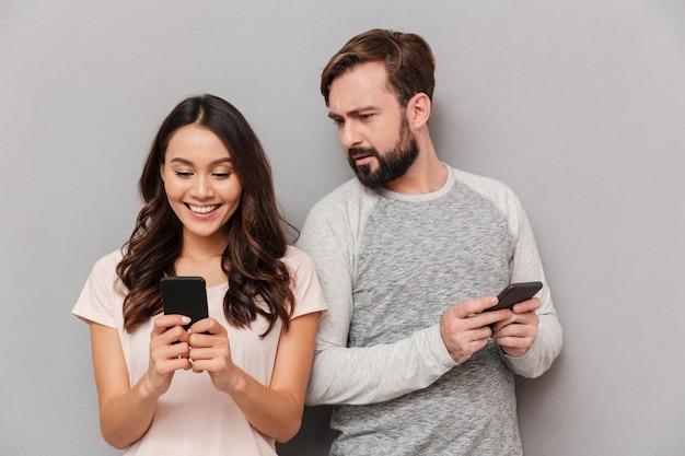 携帯電話を使用してかなり若いカップルの肖像画