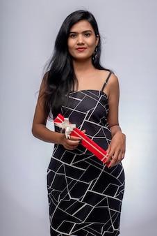 선물 상자와 함께 포즈를 취하는 예쁜 젊은 여자의 초상화