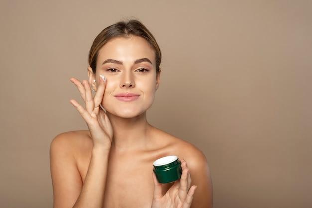 Портрет довольно молодой улыбающейся женщины с чистой свежей кожей в бежевой стене. концепция ухода за кожей и увлажнения.