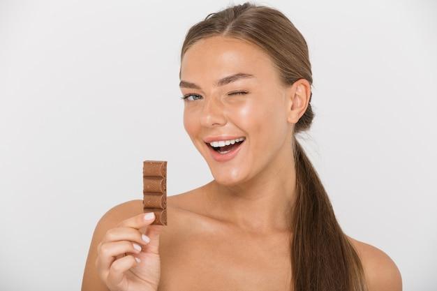 孤立した、ウィンクしているチョコレートの断片を保持しているかなり若いトップレスの女性の肖像画