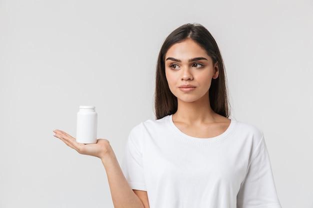 Портрет красивой молодой женщины в повседневной одежде изолирован на белом, показывая пустой контейнер