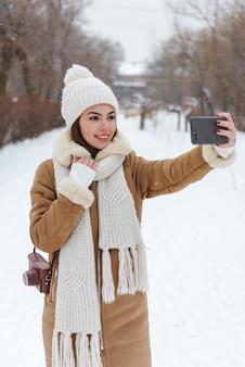 Портрет красивой молодой женщины в шляпе и шарфе, прогулки на свежем воздухе в зимний снег с помощью мобильного телефона, сделать селфи.