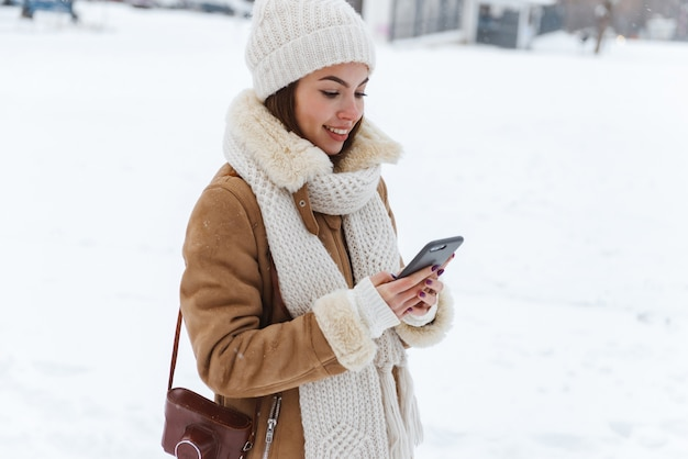 Портрет красивой молодой женщины в шляпе и шарфе, прогулки на открытом воздухе в зимний снег с помощью мобильного телефона.