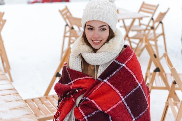 Портрет красивой молодой женщины в шляпе и шарфе, прогулки на открытом воздухе в плед зимнего снега.
