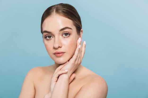 Портрет красивой молодой женщины позирует изолированной над синей стеной.