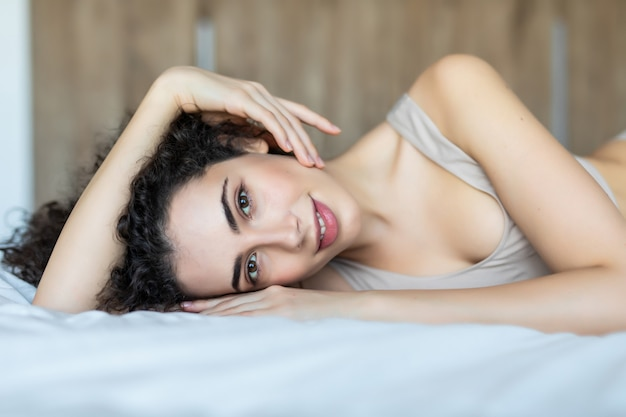 Портрет красивой молодой женщины, расслабляющейся в постели