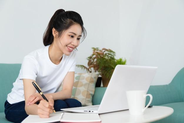 自宅でノートパソコンを持ってテーブルに座って勉強しているかなり若い女性の肖像画。