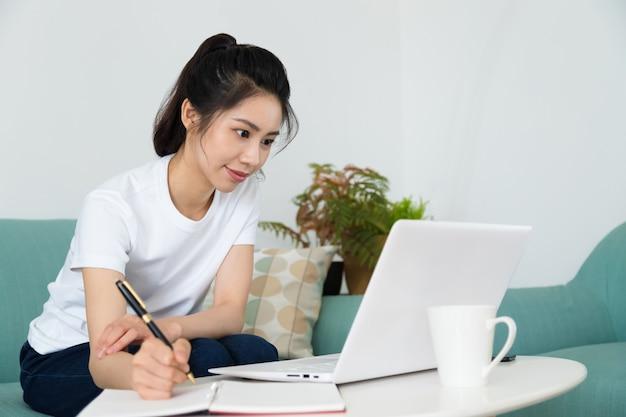 Портрет красивой молодой женщины учится, сидя за столом с ноутбуком дома