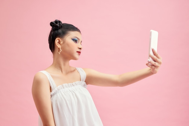 ピンクの背景に分離された携帯電話でselfieを取っているかなり若い女性の肖像画