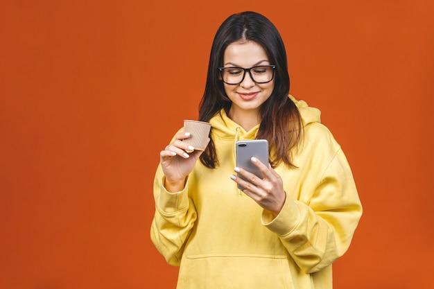 Портрет милой молодой женщины используя мобильный телефон пока держащ на вынос кофейную чашку изолированный над оранжевой предпосылкой.