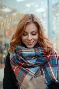 화환의 벽에 감금소에 모직 따뜻한 스카프와 검은 장갑에 검은 세련된 코트에 아름다운 미소로 예쁜 젊은 여자의 초상화. 행복 한 긍정적 인 소녀