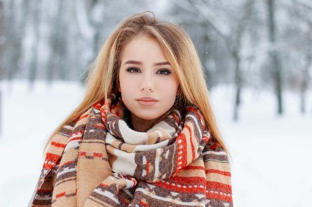 눈 덮인 공원에서 모직 빈티지 따뜻한 스카프에 긴 금발 머리를 가진 아름다운 화장과 갈색 눈을 가진 예쁜 젊은 여자의 초상화. 산책에 귀여운 소녀입니다.