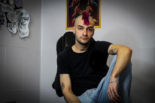 그의 studio.portrait에 있는 전문 문신 예술가 펑크 남자의 초상화. 보라색 문장을 가진 소년의 초상화.