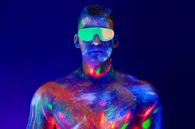 Портрет накачанного человека на дискотеке. флуоресцентная краска на лице в уф-свете