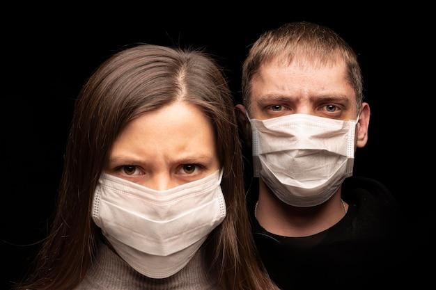 白い医療マスクのクローズアップで子犬の肖像画。ウイルスの拡散と保護の危険。未来への恐怖