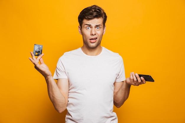 携帯電話を持っている困惑した若い男の肖像画