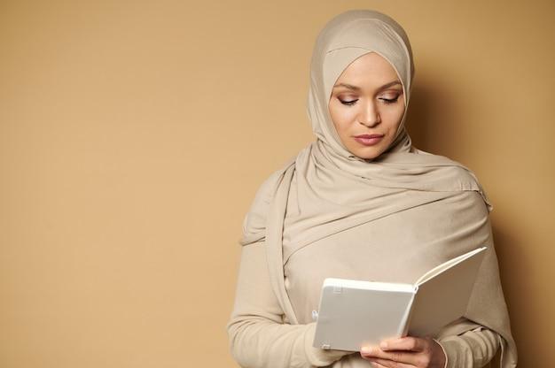 ヒジャーブを身に着け、彼女の手で白い本を読んで頭を下に傾けて静かなイスラム教徒の女性の肖像画