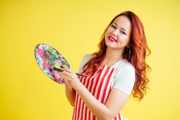 スタジオで黄色の背景にパレットとブラシを保持しているエプロンで赤髪の美しいアーティストの肖像画