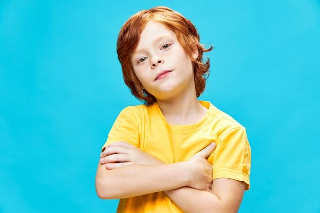 그의 팔을 가진 빨간 머리 소년의 초상화는 그 앞에서 넘어 노란색 티셔츠 자른 뷰 클로즈업