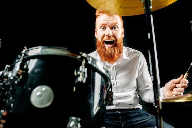 Портрет рыжеволосого эмоционального человека, играющего на барабанах и тарелках и держащего палку.