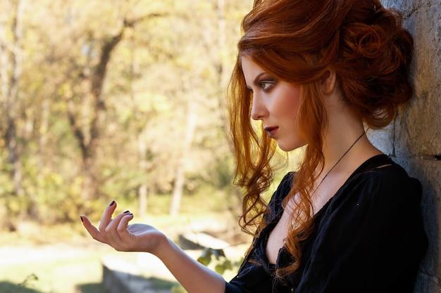 ハロウィーンのためのメイクアップと髪型を持つ赤毛の女性の肖像画