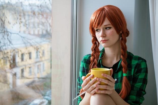 窓辺に座って黄茶のマグカップを持っている緑のシャツを着た赤毛の少女の肖像画...