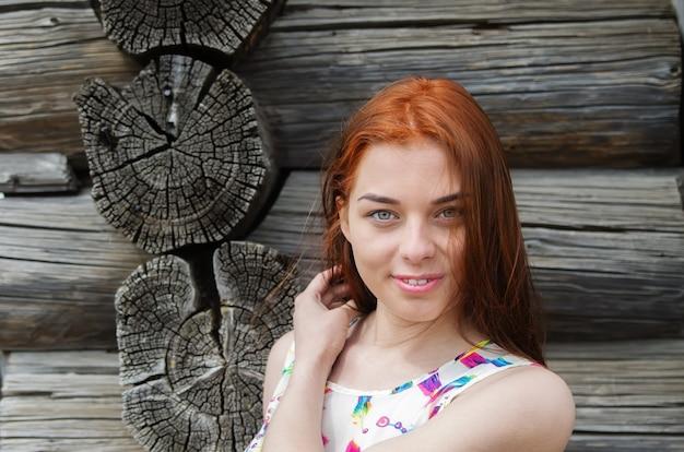 나무 집 벽에 여름 드레스에 redhaired 여자의 초상화