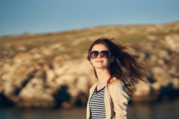 夏の自然の山のサングラスで赤髪の女性の肖像画
