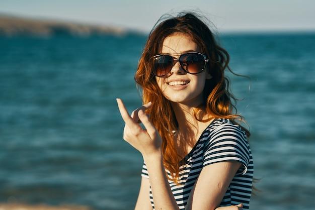 海の近くの山と笑顔の旅行観光でサングラスをかけた赤毛の女性の肖像画