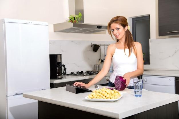 タブレットpcを見ながらキッチンでスライスする赤毛の女の子の肖像画。