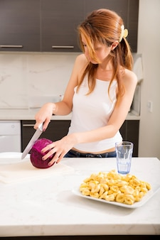 キッチンでスライスする赤毛の少女の肖像画。