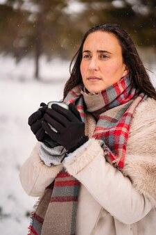 Портрет расслабленной женщины, одетой в пальто, позирует во время снегопада