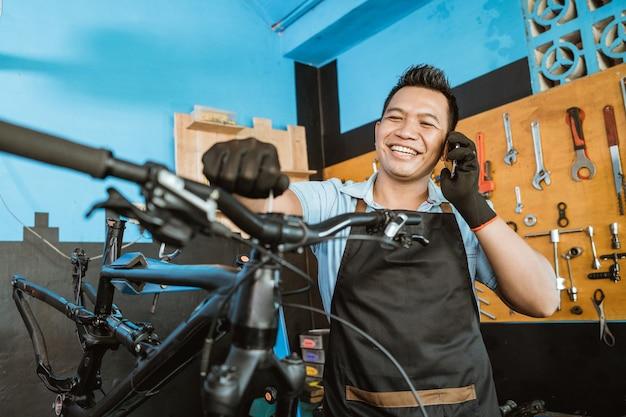 자전거를 수리하는 동안 휴대폰으로 전화를 받는 앞치마를 입은 수리공의 초상화