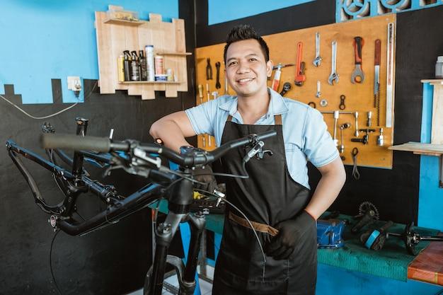 자전거 수리점에 기대어 앞치마를 입은 수리공의 초상화