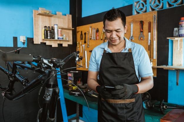 자전거를 수리하는 동안 휴대폰을 사용하는 앞치마를 입은 수리공의 초상화