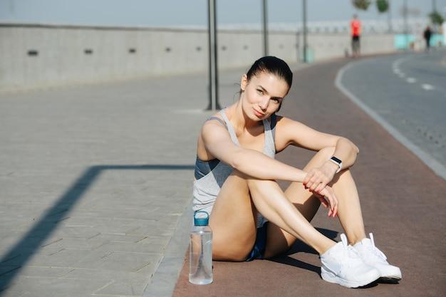 야외 트랙에 앉아 운동복을 입은 운동복을 입은 쉬고 있는 운동 여성의 초상화가 미묘한 가짜 미소로 카메라를 바라보고 있습니다. 맑고 푸른 하늘 아래 화창한 날.
