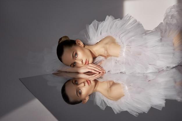 Портрет романтичной красивой женщины в легком платье отражается в зеркале