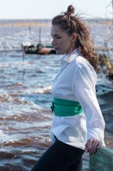 白いシャツと緑のベルトで晴れた日に湖に立っているロシアの美しい女性の肖像画