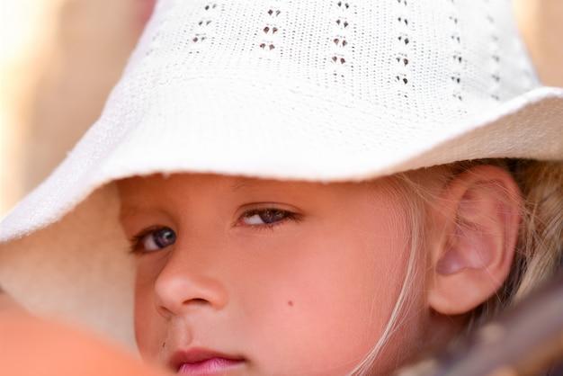 Портрет грустно и романтично девочка в белой шляпе на пляже